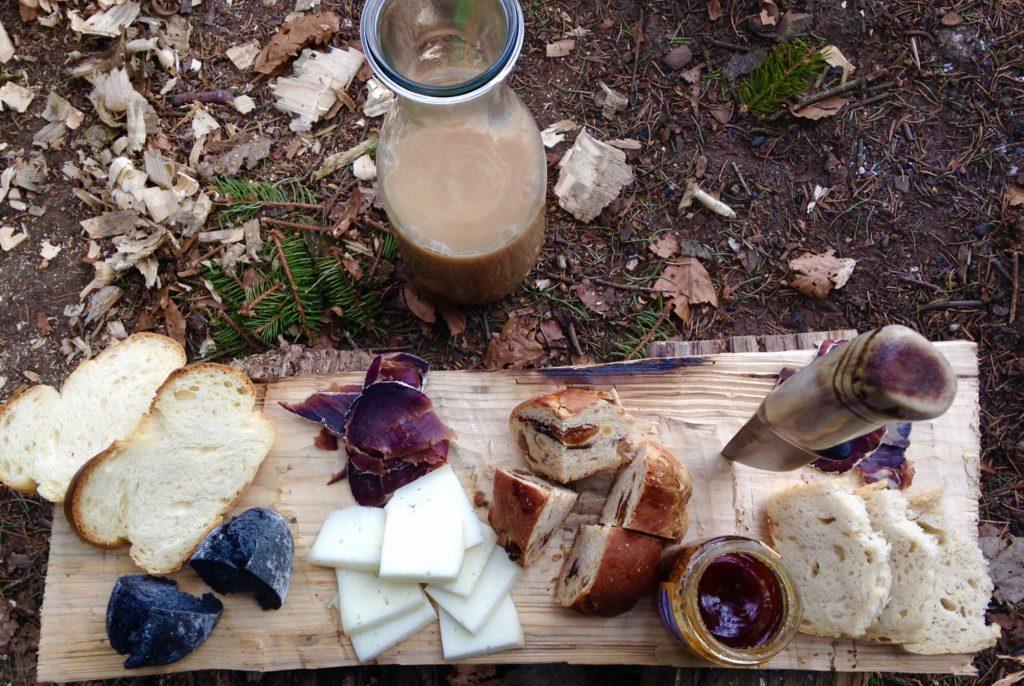 Auf einem Holzbrett liegen Zopfscheiben, Käste, getrocknetes Fleisch und Marmeladengläser.