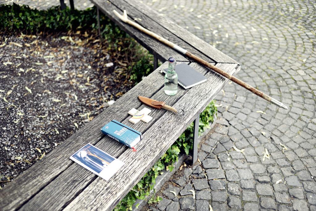 """Die """"Überlebensmittel"""" von Matthias im Wald: Jagdmesser, Bibel. Trinkflasche, Schreibzeug, Pilgerstab..."""